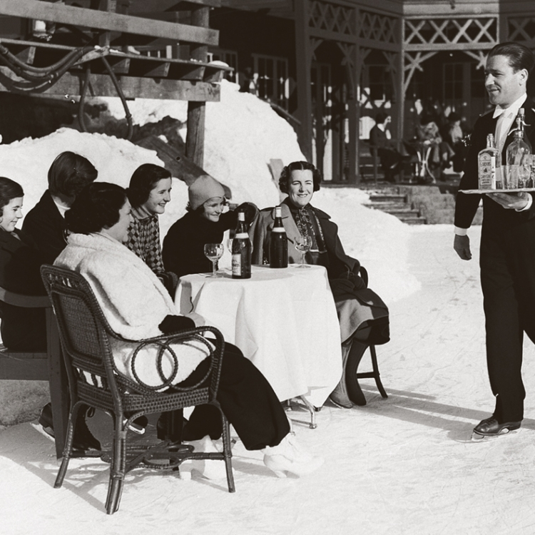 © Zeitreisen - Legendäre Orte, Routen und Momente, erscheint im April 2017 bei teNeues, € 49,90, www.teneues.com. Ein Kellner in St. Moritz bringt englischen Ladys Gin und Soda auf Schlittschuhen, 1920er-Jahre, Photo © Hulton-Deutsch Collection/CORBIS/Corbis via Getty Images. Usage on conditions above till February 23, 2020, afterwards to be requested at Getty, image fee will be invoiced directly from them.