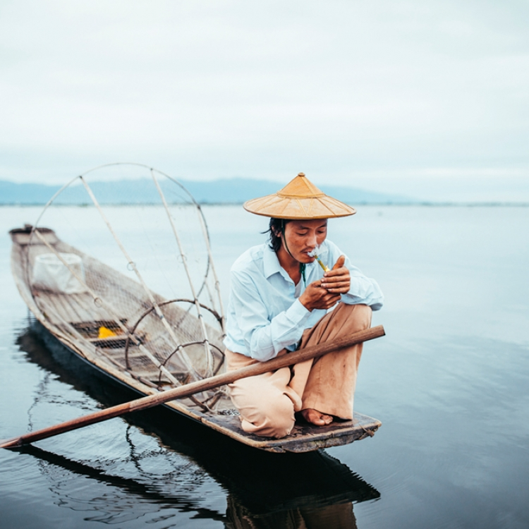 A fisherman lights up a cigarette during a morning run on Inle Lake, Myanmar, Photo © 2019 Pie Aerts. All rights reserved.
